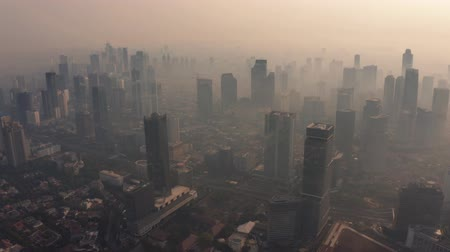 central business district : JAKARTA, Indonesia - August 27, 2019: Aerial footage of air pollution fog around office buildings in business district on the morning. Shot in 4k resolution from a drone flying forwards