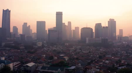flying upwards : JAKARTA, Indonesia - August 27, 2019: Aerial Jakarta skyline with dangerous air pollution fog and silhouette of modern buildings. Shot in 4k resolution from a drone flying upwards Stock Footage