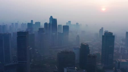 central business district : JAKARTA, Indonesia - August 27, 2019: Aerial scenery of dangerous air pollution smog with silhouette of skyscrapers in business district. Shot in 4k resolution from a drone flying forwards Stock Footage