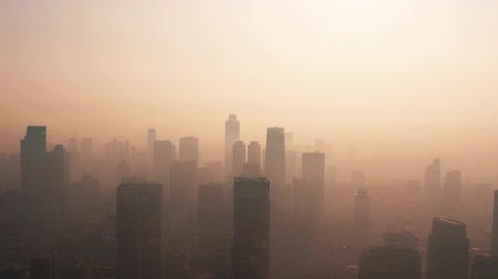 forwards : JAKARTA, Indonesia - August 27, 2019: Aerial landscape with bad air pollution and silhouette of skyscrapers in business district on the morning. Shot in 4k resolution from a drone flying forwards