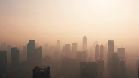 forwards : JAKARTA, Indonesia - August 27, 2019: Beautiful aerial landscape of central business district with dangerous air pollution haze at day. Shot in 4k resolution from a drone flying forwards