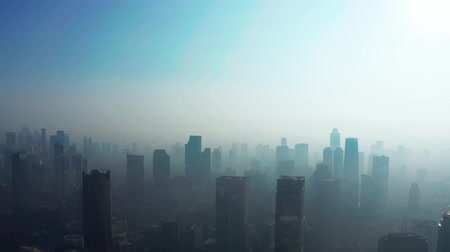 forwards : JAKARTA, Indonesia - August 27, 2019: Exotic aerial view of dangerous air pollution smoke with silhouette of skyscrapers in central business. Shot in 4k resolution from a drone flying forwards