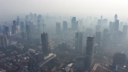 forwards : JAKARTA, Indonesia - August 27, 2019: Aerial drone view with dense air pollution smoke around office buildings on the morning. Shot in 4k resolution from a drone flying forwards