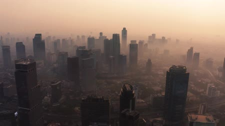 contaminação : JAKARTA, Indonesia - August 27, 2019: Aerial view of dense air pollution smoke around skyscrapers in business district at the morning. Shot in 4k resolution from a drone flying forwards Vídeos