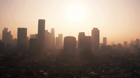 central business district : JAKARTA, Indonesia - August 27, 2019: Jakarta aerial skyline with smoke of air pollution and silhouette of skyscrapers at sunrise. Shot in 4k resolution from a drone flying forwards Stock Footage