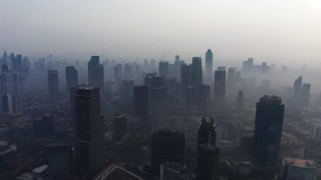 глобальное потепление : JAKARTA, Indonesia - August 27, 2019: Aerial scenery of business district on the morning with air pollution fog and silhouette of skyscrapers. Shot in 4k resolution from a drone flying forwards