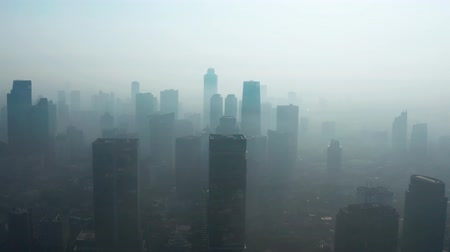forwards : JAKARTA, Indonesia - August 27, 2019: Aerial view of silhouette of skyscrapers with dense air pollution haze in business district on the morning. Shot in 4k resolution from a drone flying forwards Stock Footage