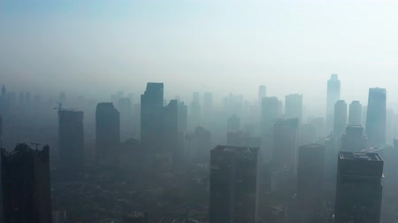 contaminação : JAKARTA, Indonesia - August 27, 2019: Aerial view of unhealthy city with dense air pollution smoke and silhouette of skyscrapers. Shot in 4k resolution from a drone flying forwards