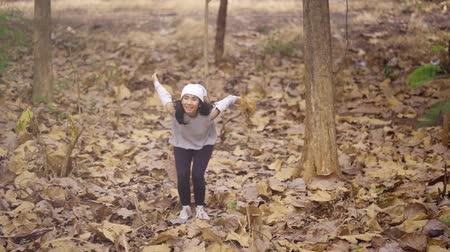 knitted : Slow motion of happy woman jumping at the autumn park with dried autumn leaves. Shot outdoors