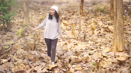 gebreid : Slow motion of happy woman walking on the autumn park with dried autumn leaves. Shot outdoors
