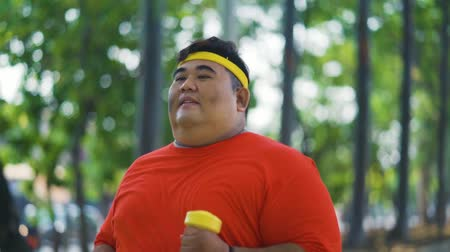 headband : Slow motion of obese man running at the park while holding dumbbells. Shot outdoors Stock Footage