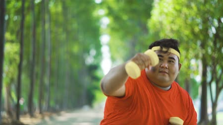 saç bantı : Slow motion of attractive overweight man doing boxing exercise while holding dumbbells at the park Stok Video