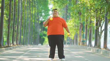 saç bantı : Overweight young man exercising with dumbbells while standing at the park. Shot in 4k resolution