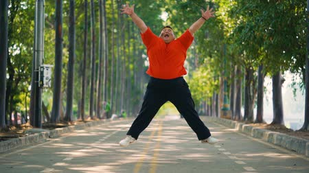 headband : Slow motion of overweight young man jumping on the park while wearing sportswear at the morning Stock Footage