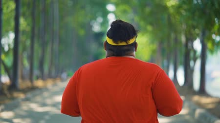 headband : Rear view slow motion of overweight young man jogging for losing weight at the park on the morning