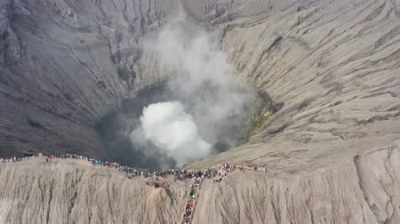 erupção : Exotic aerial view of Mount Bromo crater with fumes on the morning. Shot in 4k resolution from a drone flying from right to left