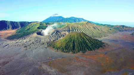 erupção : Beautiful aerial view of Mount Bromo national park with sea of the sand and the mountain peak. Shot in 4k resolution from a drone flying from left to right Vídeos