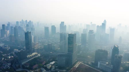 forwards : JAKARTA, Indonesia - September 04, 2019: Beautiful aerial view of air pollution smog covering Jakarta downtown and skyscrapers on the morning. Shot in 4k resolution from a drone flying forwards