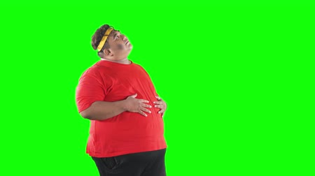 headband : Hungry overweight man imagine tasty foods while stroking his belly in the studio. Shot in 4k resolution with green screen background