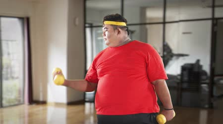 gewichtheffen : Digital composite of overweight man exercising with dumbbells in the fitness center. Shot in 4k resolution Stockvideo