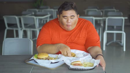 hranolky : Overweight man sitting in the restaurant while enjoying junk foods on the table. Shot in 4k resolution