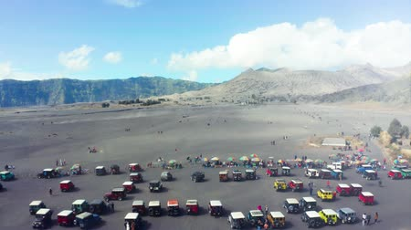erupção : East Java, Indonesia - September 04, 2019: Beautiful aerial view of tourism jeep gather around sea of the sand in Mount Bromo national park. Shot in 4k resolution