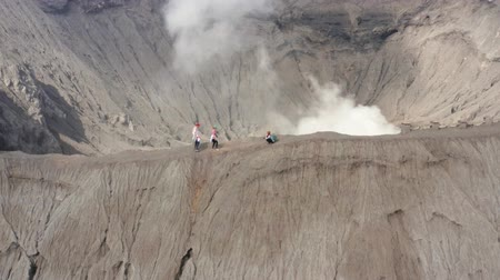 erupção : East Java, Indonesia - September 04, 2019: Aerial view of tourist walking on the edge of Mount Bromo crater. Shot in 4k resolution from a drone flying from left to right