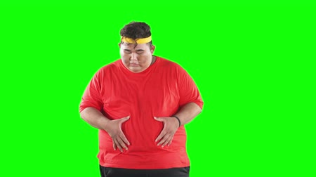 starving : Unconfident overweight man standing in the studio while looking and touching his belly. Shot in 4k resolution with green screen background Stock Footage