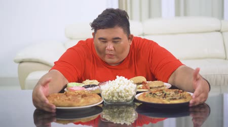 ganancioso : Greedy overweight man taking delicious junk foods on the table at home. Shot in 4k resolution