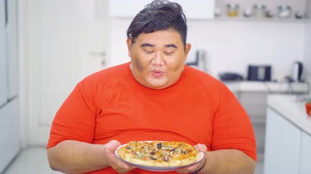жадный : Hungry overweight man holding and looking a plate of delicious pizza in the kitchen at home. Shot in 4k resolution