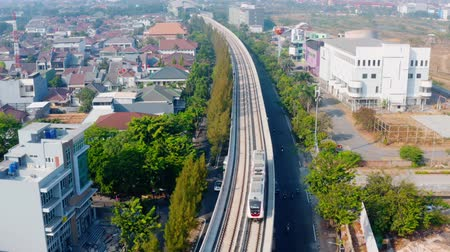rapid transit : JAKARTA, Indonesia - September 10, 2019: Beautiful aerial landscape of Jakarta MRT moving on the elevated track on the morning. Shot in 4k resolution from a drone flying forwards