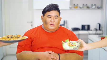 decidir : Overweight man choosing a bowl of vegetable salad offers and refuse a plate of pizza in the kitchen at home. Shot in 4k resolution