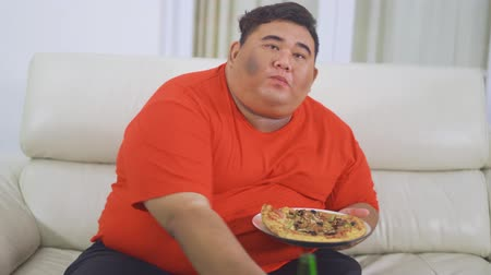 voracious : Overweight man eating pizza and drinking a bottle of beer while sitting on the sofa in living room at home. Shot in 4k resolution