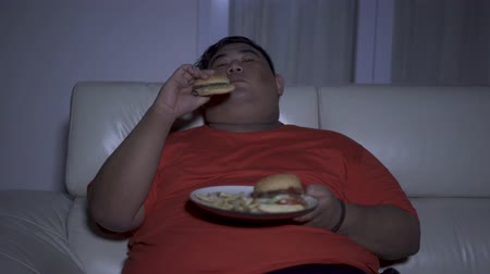 voracious : Greedy overweight man eating a plate of burger while sitting on the sofa and watching tv at night in living room. Shot in 4k resolution