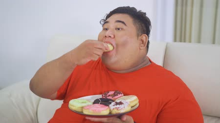 voracious : Overweight man enjoying a plate of sweet donuts while sitting on the sofa in the living room at home. Shot in 4k resolution