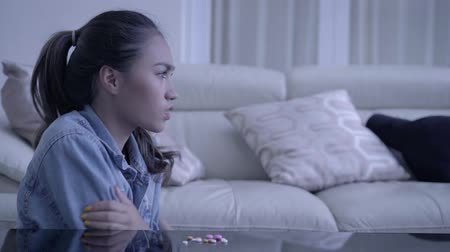 addiction recovery : Teenage girl drugs addict sitting in the living room while shivering with medicines or drugs on the table at home. Stock Footage
