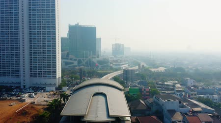 rapid transit : JAKARTA, Indonesia - September 10, 2019: Aerial view of Jakarta MRT station on the elevated track in misty morning. Shot in 4k resolution from a drone flying forwards