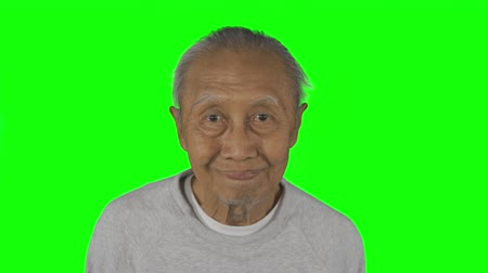 nevetséges : Elderly man with wrinkled skin making funny face expression in the studio. Shot in 4k resolution with green screen background