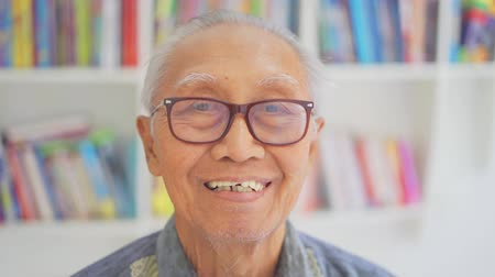 книжный шкаф : Happy elderly man smiling at the camera while wearing glasses in the library. Shot in 4k resolution