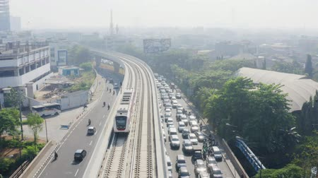 rapid transit : JAKARTA, Indonesia - September 10, 2019: Aerial landscape of Jakarta MRT moving on the elevated track above the road on the morning. Shot in 4k resolution from a drone flying backwards