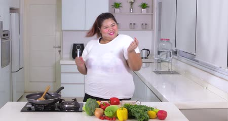 brokkoli : Happy overweight woman slicing vegetables while dancing in the kitchen at home. Shot in 4k resolution Stock mozgókép