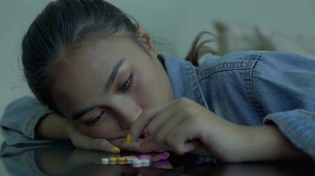 addiction recovery : Addicted teenage girl looks depressed counting drugs on the table at home. Shot in 4k resolution