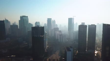 flying upwards : JAKARTA, Indonesia - September 13, 2019: Beautiful aerial view of Jakarta business district with silhouette of skyscrapers and air pollution smoke. Shot in 4k resolution from a drone flying upwards