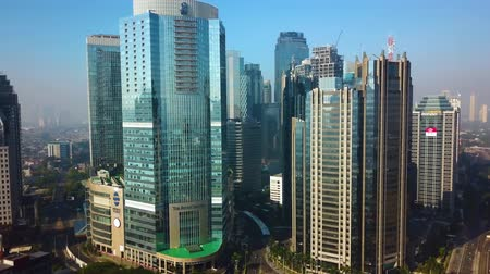высокое разрешение : JAKARTA, Indonesia - September 13, 2019: Aerial view of modern office buildings exterior with glass windows in business district. Shot in 4k resolution from a drone flying from left to right