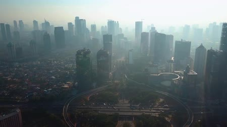 contaminação : JAKARTA, Indonesia - September 13, 2019: Beautiful aerial view of Semanggi bridge and silhouette of skyscrapers with air pollution fog at morning. Shot in 4k resolution from a drone flying forwards Vídeos