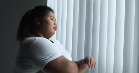 nejistota : Unhappy overweight woman standing near the window while thinking something at home. Shot in 4k resolution