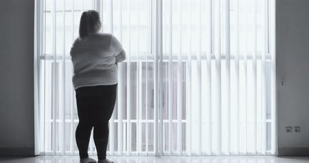 gordijn : Silhouette of moody overweight woman standing alone near the window at home. Shot in 4k resolution
