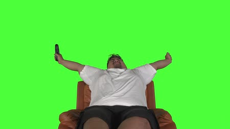 Overweight young man stretching his arms during watching TV and sleeping on the sofa. Shot in 4k resolution with green screen background