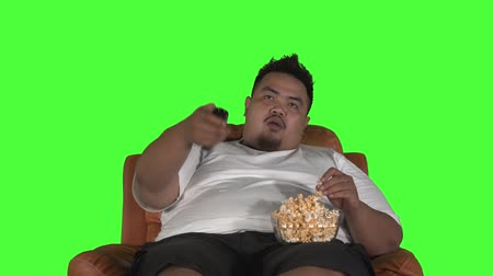 жадный : Overweight young man watching TV while eating a bowl of popcorn on the sofa. Shot in 4k resolution with green screen background