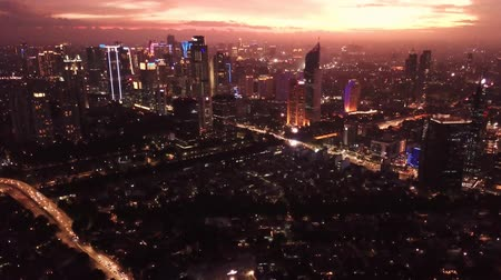 flying upwards : JAKARTA, Indonesia - October 22, 2019: Beautiful aerial view of twilight time with silhouette of modern buildings and dramatic sky. Shot in 4k resolution from a drone flying upwards Stock Footage